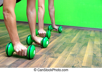 fitness training with dumbbell - group of girls exercising...