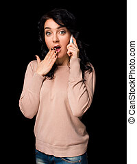 Shocked young woman talking on cell phone