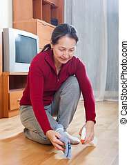 mature housewife polishing parquet floor with polish