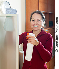 Woman dusting furniture - mature woman dusting glass on...