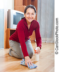 Smiling mature woman rubing parquet floor with furniture...