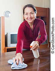 mature woman dusting wooden table with rag and cleanser at...