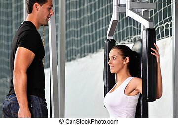 woman in the fitness gim working out with personal trainer...