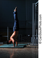 young man performing handstand in fitness studio