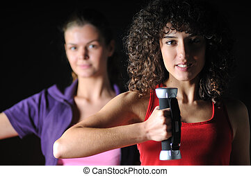 two girls working out in fitness club