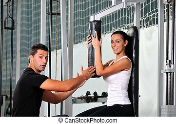 woman in fittness club with trainer - woman in the fitness...