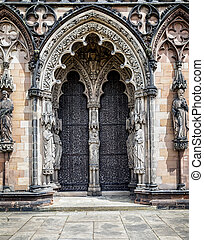 Medieval Cathedral doors surrounded by religious statues.