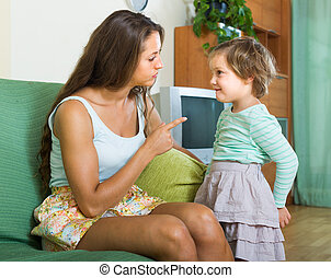 Woman scolding child at home - Young woman scolding little...
