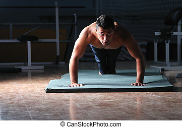young man with strong arms working out in gym