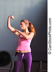 young woman with strong arms rising hands in air and...