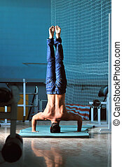 Young man performing handstand in fitness studio rear, back...