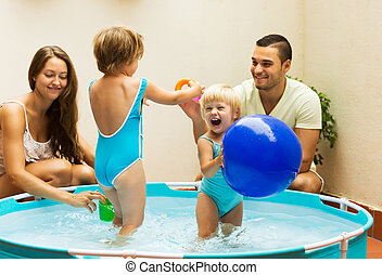 Children and parents playing in pool