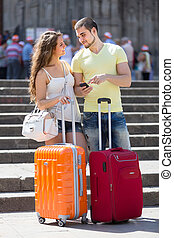 Couple with GPS navigator and baggage - Young positive...