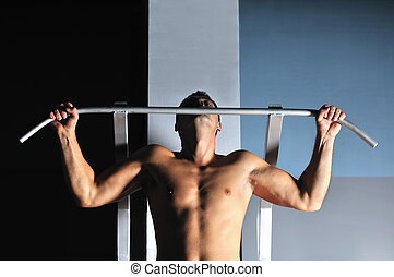 young man with strong arms working out in gym and...