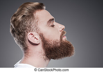 Bearded handsome. Side view of handsome young bearded man...