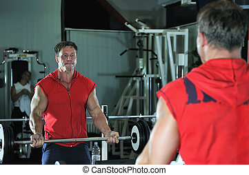 Strong man work out in gym - Strong young man work out in...
