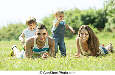 Family of four in grass at park