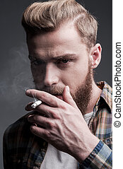 Man smoking Handsome young bearded man smoking a cigarette...