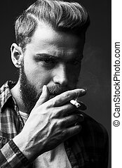 Bearded man smoking. Black and white portrait of handsome...