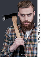 Just me and my axe Confident young bearded man carrying a...
