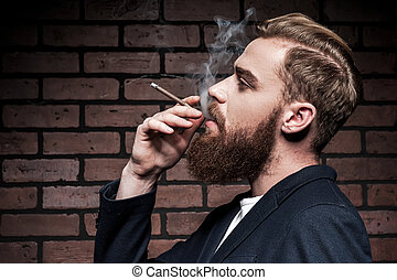 In his own style. Side view of handsome young bearded man smoking a cigarette while standing against brick wall