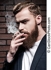 Beard man smoking. Handsome young bearded man smoking a...