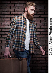 Ready to go. Handsome young bearded man carrying suitcase...