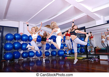 happy fitness - happy girls jumping in fitness cloub