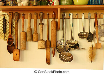Wooden and metal kitchen ware hanging on the wall. - Wooden...