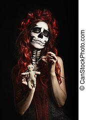 Young woman with calavera makeup (sugar skull) piercing...