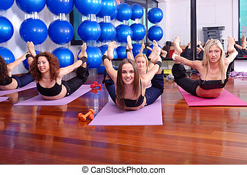 yoga - health club: women doing stretching, fitness,...