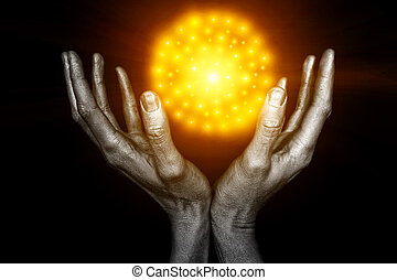 Silvery male hands with a yellow energy ball on a black...