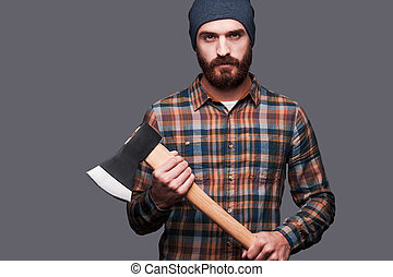 Serious lumberjack Confident young bearded man holding a big...