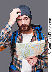 Lost in somewhere. Frustrated young bearded man carrying...