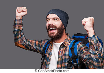 I did it Happy young bearded man carrying backpack and...
