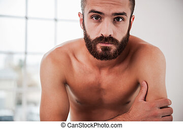 Bearded handsome. Confident young bearded and shirtless man...