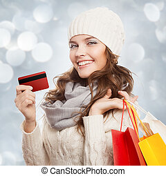 Shopping happy woman holding bags and credit card Winter...