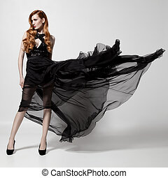 Fashion woman in fluttering black dress White background