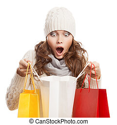 Shopping surprised woman holding bags Winter sales