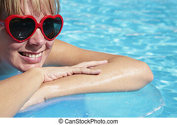 Summer Pool - Portrait of a woman on a lilo in a pool