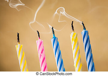 Five blow out candles over yellow background