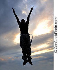 young man jumping in air outdoor at night ready for party -...