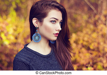 Portrait of young beautiful woman in autumn park. Beauty....