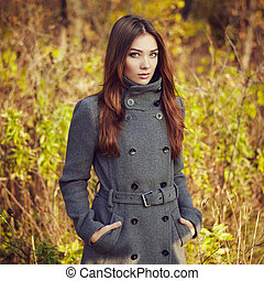 Portrait of young beautiful woman in autumn coat. Fashion...
