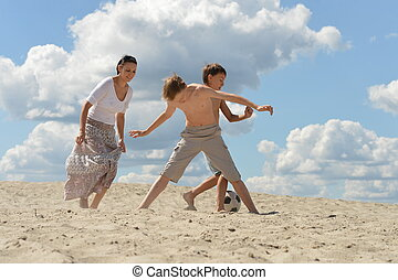 Happy family playing football on beach in summer day