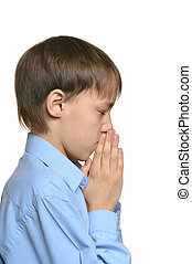 Young sad praying boy standing isolated on white background