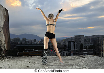 young gogo dancer girl on top of the building with city in backgound