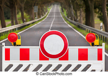 Closed Road - Red and white colored street barrier at an...
