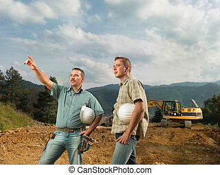 engineers supervising construction in progress - two...