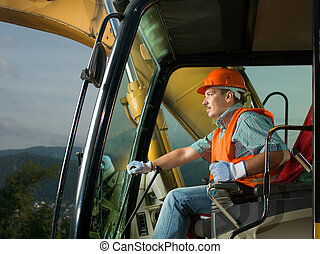 happy excavator driver - male operator driving excavator on...